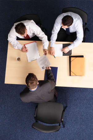 hiring:   A young man at a a job interview with two interviewers, showing them his resume.Aerial shot taken from directly above the table.