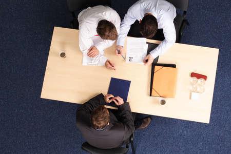 comit� d entreprise: Un jeune homme � lune entrevue demploi avec deux interviewers, leur montrant son resume.Aerial a tir� pris de directement au-dessus de la table. Banque d'images