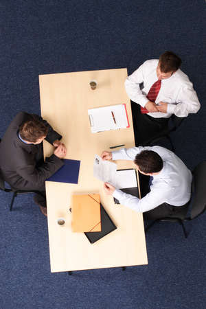 headhunting: A young man at a a job interview with two interviewers, showing them his resume.Aerial shot taken from directly above the table. Stock Photo