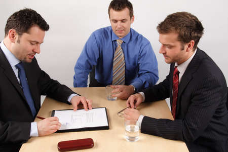 buy shares: Three businessmen handling negotiations.