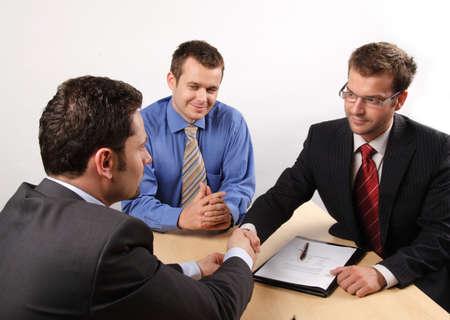 comité d entreprise: Trois hommes d'affaires assis à une table de négociation et la signature d'un contrat. handskake.  Banque d'images