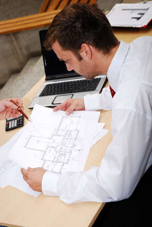 male architect working with blueprints in the office photo