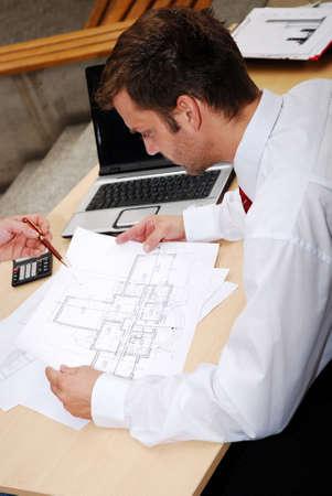 maschio architetto con schemi di lavoro in ufficio