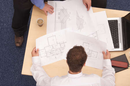 confer: Two architects working on blueprints.