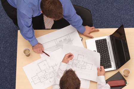 Two architects working on blueprints.
