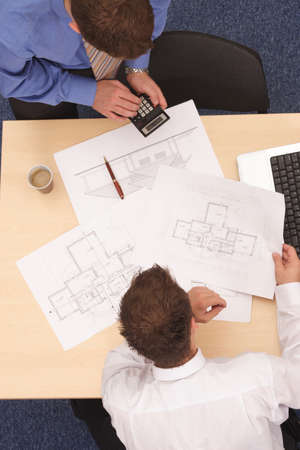 executive apartment: Aerial view of two businessmen calculating the plans.