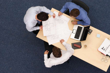 reviewing:   three young executives siting,standing and discussing overblueprints .Aerial shot taken from directly above the table.