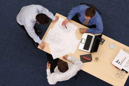 tres jóvenes ejecutivos de emplazamiento, de pie y debatir overblueprints. aérea disparó adoptadas directamente por encima de la mesa.