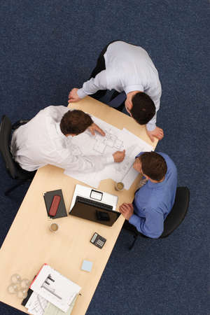 confer:   three young executives siting,standing and discussing overblueprints .Aerial shot taken from directly above the table.