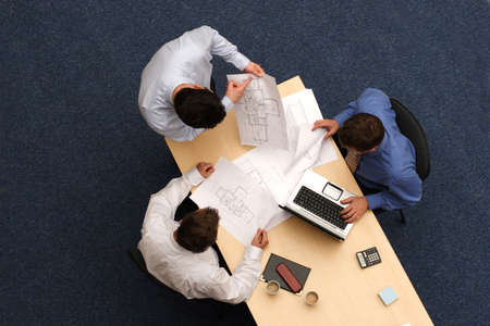 the council:   three young executives siting,standing and discussing overblueprints .Aerial shot taken from directly above the table.