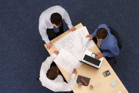directly:   three young executives siting,standing and discussing overblueprints .Aerial shot taken from directly above the table.