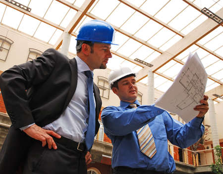 technology deal: Two architects reviewing the blueprints Stock Photo