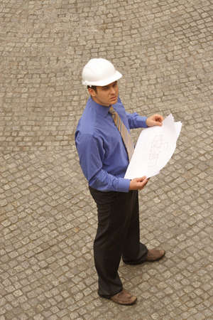 technology deal: Young architect in hardhat standing on pavement with blueprints