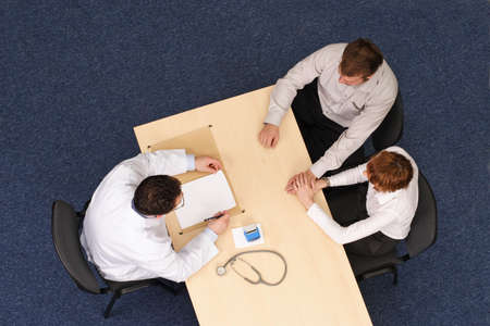 arzt gespr�ch: Eine Ansicht von oben ein paar Sitzung gegen�ber einem Arzt an seinem Tisch w�hrend einer �rztlichen Konsultation. Arzt sprechen Gesundheitsakte