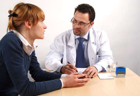 psychiatrist:   Doctor and young woman patient talking to each other durring visit in the office