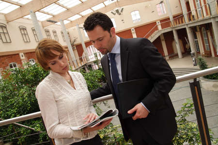 confer: Business man and woman meeting in hall of building Stock Photo