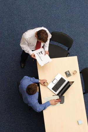 discutere: Due giovani di sesso maschile dirigenti discutere un progetto in ufficio.