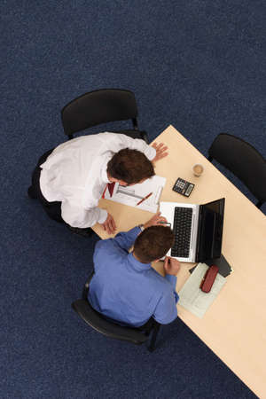 confer: Two young male executives discuss a project in the office.