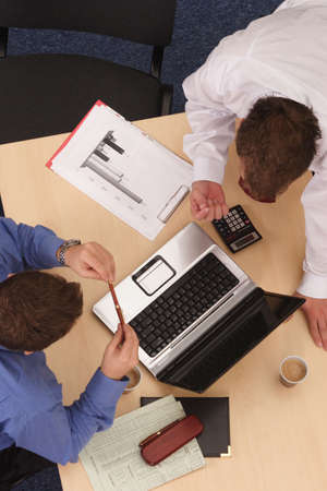 talking about details.An overhead shot of two male executives in a business meeting. photo