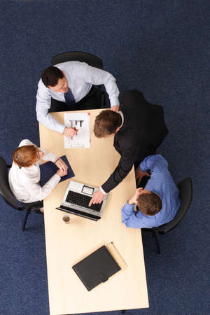 confer: four business people meeting, four are stiting, one is standing at the desk .Aerial shot taken from directly above the table