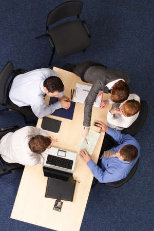 confer:   five business people meeting, four are stiting, one is standing at the desk .Aerial shot taken from directly above the table.