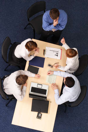 five business people meeting, four are stiting, man is standing at the desk .Aerial shot taken from directly above the table. photo
