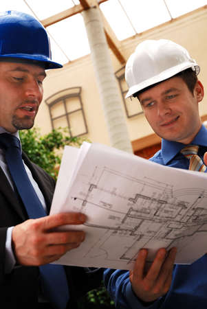 reviewing: Two architects reviewing the blueprints Stock Photo
