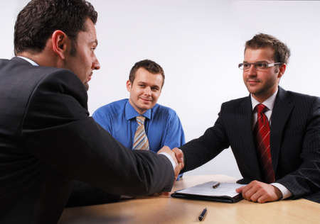 mediation:    Three businessmen sitting at a table negotiating and signing a contract. handskake. Stock Photo