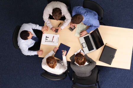 leadership - Five Businesspeople gathered around a table for a meeting, brainstorming. Aerial shot taken from directly above the table. Stock Photo