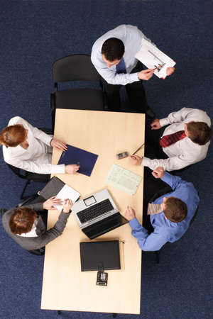 assessments: presentation - Five Businesspeople gathered around a table for a meeting, brainstorming. Aerial shot taken from directly above the table.