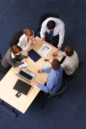 business coaching - Five Businesspeople gathered around a table for a meeting, brainstorming. Aerial shot taken from directly above the table. photo
