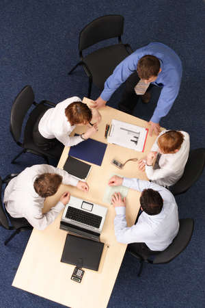 Five Businesspeople gathered around a table for a meeting, brainstorming. Aerial shot taken from directly above the table. photo