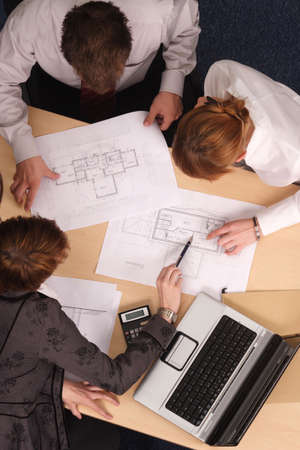directly:   Architect showing couple of clients blueprints in the office.Aerial shot taken from directly above the table.
