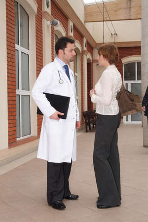 A young woman and a male doctor stand outside a building, having a conversation. photo