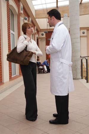 questionnement: Une jeune femme et un docteur masculin se tiennent en dehors dun b�timent, ayant une conversation. Banque d'images