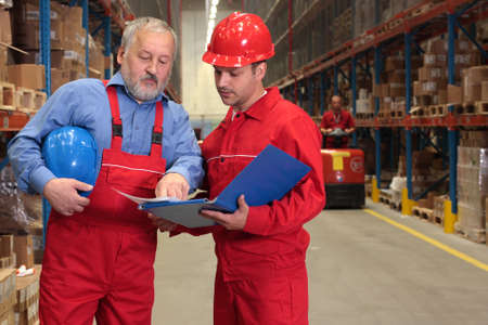two workers in uniforms in warehouse photo