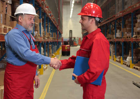 two workers in uniforms in warehouse - handshake Stock Photo - 3232340