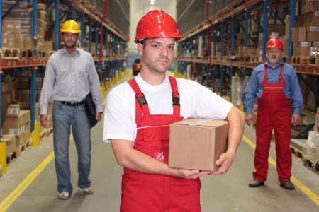 worker in hardhat with parcel at the front of team  of workforce  in warehouse photo
