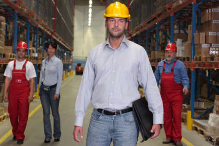 warehouse equipment: manager with briefcase at the front of team  of workforce  in warehouse - 4 people