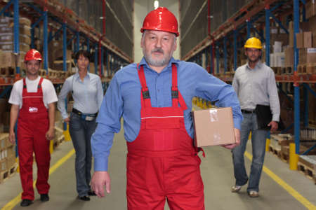 mature worker with parcel at the front of team  of workforce  in warehouse photo