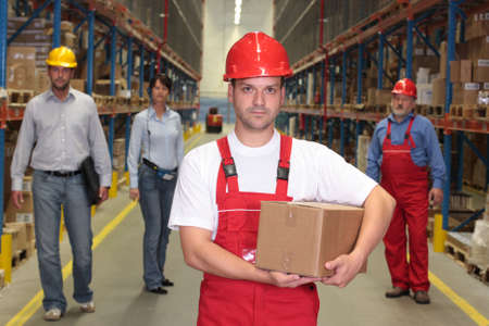 experienced operator: man with parcel at the front of team  of workforce  in warehouse