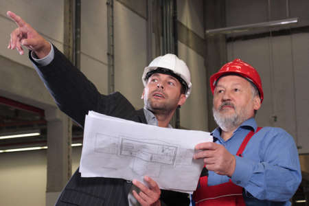 review site: businessmen and older worker, wearing hardhats looking at a set of blueprints and discussing a construction project.