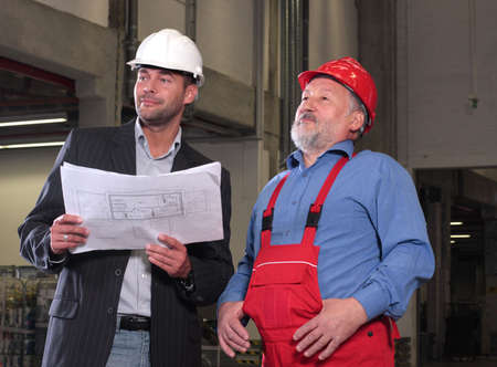 project deadline: businessmen and older worker, wearing hardhats looking at a set of blueprints and discussing a construction project.
