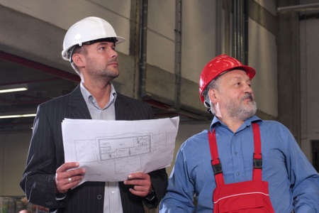 businessmen and older worker, wearing hardhats looking at a set of blueprints and discussing a construction project. photo