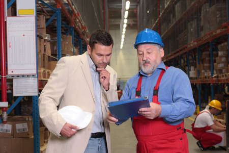 manager and older worker talking over papers in warhouse Stock Photo