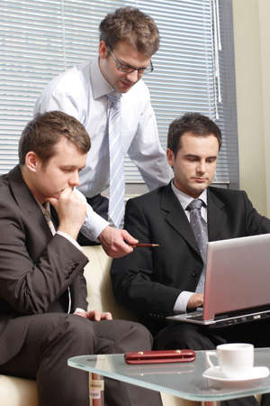 Three young business men working  together with laptop in the office photo