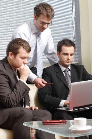 discutere: Tre giovani uomini d'affari in collaborazione con computer portatile in ufficio  Archivio Fotografico