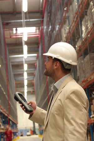 finished: An inspector with scanner in a factory maintaining stocks of finished products on the shelves in a storeroom.