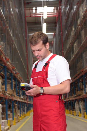 scanner: A worker with scanner in a factory looking at stocks of finished products on the shelves in a storeroom.