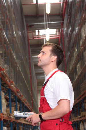 storeroom: A worker with bar code reader in a factory looking at stocks of finished products on the shelves in a storeroom. Stock Photo